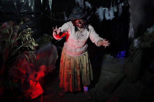 """La indígena Evelin Huaycho, posa como una """"Cholita"""" zombi a fin departicipar en la Casa del Horror en las fiesta de Halloween en El Alto, Bolivia, el miércoles 30 de octubre de 2013. Una década después de aterrizar en Bolivia y tras años de debate entre defensores y detractores, la fiesta de Halloween ha comenzado a fusionarse con personajes y leyendas andinas como la cholita encantada o zombi. (AP Photo/Juan Karita)"""