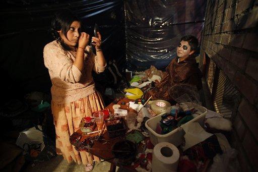 """La indígena Evelin Huaycho, izquierda, se aplica maquillaje vestida como una """"Cholita"""" zombi para participar en la Casa del Horror en las fiesta de Halloween en El Alto, Bolivia, el miércoles 30 de octubre de 2013. Una década después de aterrizar en Bolivia y tras años de debate entre defensores y detractores, la fiesta de Halloween ha comenzado a fusionarse con personajes y leyendas andinas como la cholita encantada o zombi. (AP Photo/Juan Karita)"""