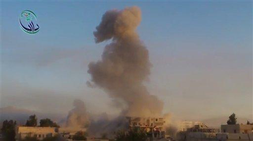En esta imagen tomada de un video obtenido por Shaam News Network, que ha sido verificada sobre la base de su contenido y reportes de la AP, se ve una columna de humo ascender de edificios tras la explosión de una bomba en Daraya, en las afueras de Damasco, el martes, 15 de octubre del 2013. (Foto AP/Shaam News Network via AP Video)