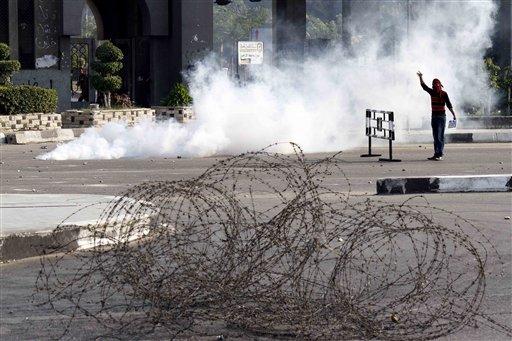 Un manifestante enmascarado en medio de una nube de gas lacrimógeno durante enfrentamientos con fuerzas de seguridad, que dispersaron a varios cientos de estudiantes universitarios partidarios del derrocado presidente Mohamed Morsi, que se manifestaban cerca de Rabaah el-Adawiya, en el este de El Cairo, el lunes 28 de octubre de 2013. (Foto AP/Said Hamdy)