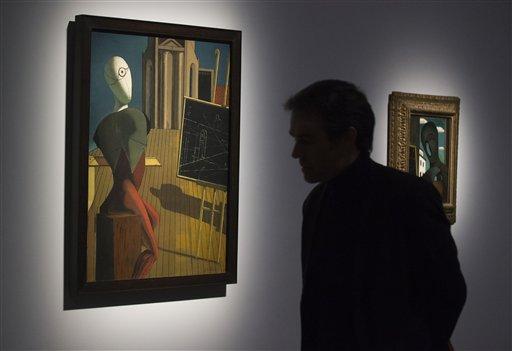 """Un hombre observa una pintura titulada """"Le Prophete, 1914-1915"""", del artista italiano nacido en grecia Giorgio de Chirico, durante una presentación a la prensa de la exhibición """"Surrealismo y el objeto"""" en el Centro Pompidou de París, el martes 28 de octubre del 2013. La muestra narra por primera vez la historia de cómo los surrealistas canalizaron su mensaje a través de bloques de madera, maniquís y otros objetos filocomunistas de uso cotidiano para cambiarle el rostro al arte del siglo XX, seduciendo a Joan Miró y Pablo Picasso. (AP Foto/Michel Euler)"""