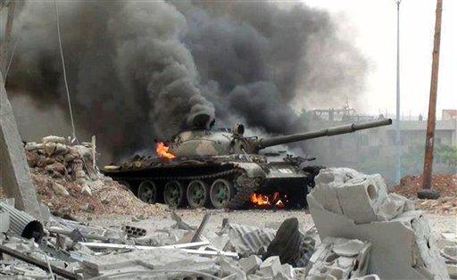 Esta imagen de periodismo ciudadano suministrada por el grupo Revolución Siria contra Bashar Assad, que ha sido autenticada con base en su contenido y otros reportes de la AP, muestra un tanque sirio en llamas durante enfrentamientos con combatientes rebeldes en Jubar, un suburbio de Damasco, Siria, el miércoles 18 de septiembre de 2013. (Foto AP/Revolución Siria contra Bashar Assad)