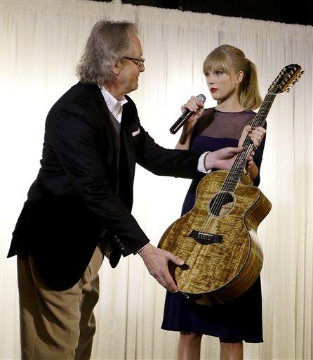 Taylor Swift entrega una guitarra para exhibición a Kyle Young, en el Museo y Salón de la Fama de la Música Country el sábado 12 de octubre de  2013, en Nashville, Tenesí. Swift inauguró en el museo el Centro Educativo Taylor Swift cuyo costo fue de 4 millones de dólares. (Foto AP/Mark Humphrey)