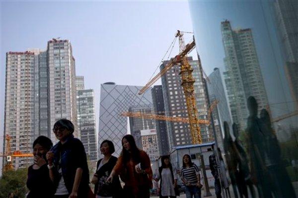 Algunas mujeres caminan junto a un sitio en construcción y edificios de oficinas durante su hora del almuerzo en Beijing, China, el martes 8 de octubre de 2013. El Fondo Monetario Internacional rebajó el martes sus pronósticos de crecimiento económico global para este año y el próximo, en especial a causa de una expansión más lenta en China, India, Brasil y otras naciones en desarrollo. (Foto AP/Andy Wong)