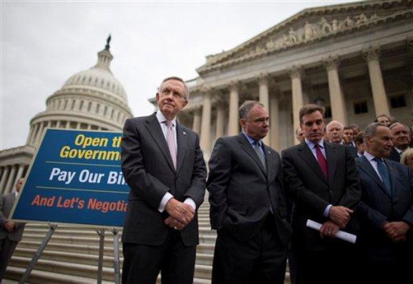 De izquierda a derecha, los legisladores demócratas Harry Reid, Tim Kaine, Mark Warner, Charles Schumer y otros, informan desde las escalinatas del Congreso sobre las negociaciones sobre el presupuesto, en Washington, el miércoles 9 de octubre de 2013. La falta de acuerdos ha provocado una parálisis parcial en el gobierno. (Foto AP/Evan Vucci)