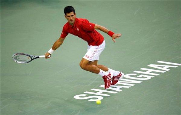 El serbio Novak Djokovic devuelve una volea al francés Jo-Wilfried Tsonga durante la semifinal del Masters de Shanghai en esa ciudad de China, el sábado 12 de octubre de 2013. Djokovic avanzó a la final de la competición al vencer 6,2, 7,5 a Tsonga. (AP Foto/Eugene Hoshiko)