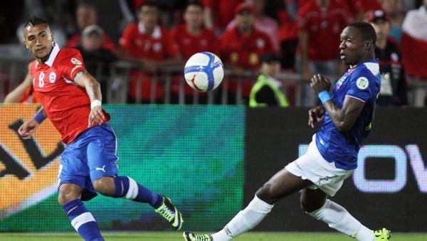 El jugador de Chile, Arturo Vidal, disputa el balón con el jugador deEcuador, Walter Ayovi, hoy, martes 15 de octubre de 2013, durante la última fecha de la clasificación sudamericana para el Mundial de Brasil 2014 en el Estadio Nacional en Santiago de Chile (Chile). EFE