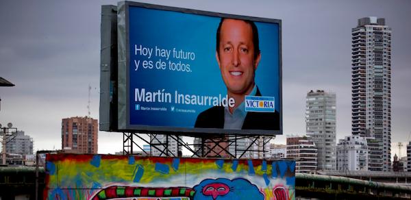 Una publicidad de campaña de Martín Insaurralde, candidato oficialista a diputado por la provincia de Buenos Aires, asoma sobre un puente en Buenos Aires, el miércoles 23 de octubre de 2013. (AP foto/Natacha Pisarenko)