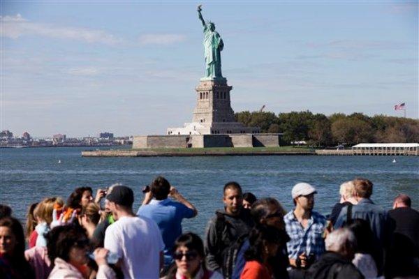Turistas pasan cerca de la Estatua de la Libertad durante un recorrido en una embarcación por diversos puntos importantes en el puerto de Nueva York, el sábado 12 de octubre de 2013. La Estatua de la Libertad fue abierta nuevamente al domingo. (AP Foto/John Minchillo)