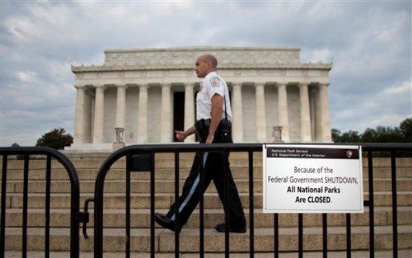"""Un agente camina por una barrera con un letrero que dice """"Todos los Parques Nacionales están cerrados debido a la paralización del gobierno"""" frente al monumento a Lincoln en Washington, el martes 1 de octubre de 2013. (AP Foto/Carolyn Kaster)"""