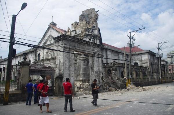 Varias personas observan la Basílica del Santo Niñoo en Cebú, en la región central de Filipinas, el martes 15 de octubre de 2013. Un terremoto de magnitud 7,2 grados provocó el derrumbe de edificios, dañó carreteras y derribó el camapanario de la iglesia más antigua del país el martes por la mañana. (Foto AP/Chester Baldicantos)
