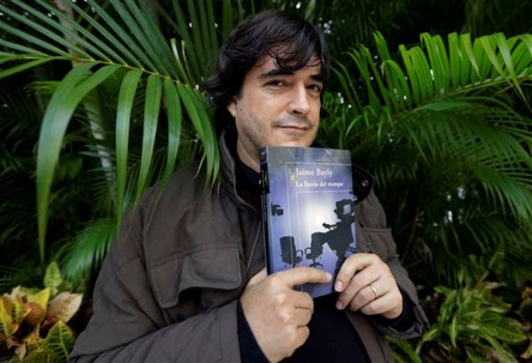 """En esta foto del 11 de noviembre del 2013, Jaime Bayly posa con un ejemplar de su más reciente libro, """"La lluvia del tiempo"""", en su casa en Key Biscayne, Florida. (AP Foto/Lynne Sladky)"""