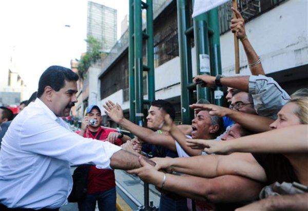 En esa foto cedida por la Oficina de Prensa de la Presidencia de Venezuela, el presidente Nicolás Maduro saluda a sus partidarios durante un mitin de trabajadores del transporte en Caracas, Venezuela, el martes 12 de noviembre de 2013.  La Asamblea Nacional, dominada por el oficialismo, aprobó el jueves 14 de noviembre en una primera discusión una ley habilitante para que Maduro emita decretos con fuerza de ley a lo largo de 12 meses.(Foto AP/Oficina de Prensa de la Presidencia)
