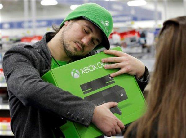 Emanuel Jumatate, de Chicago, abraza la caja de su nueva consola Xbox One después de comprarla en una tienda de la cadena Best Buy el viernes 22 de noviembre de 2013, en Evanston, Illinois. (Foto AP/Nam Y. Huh)