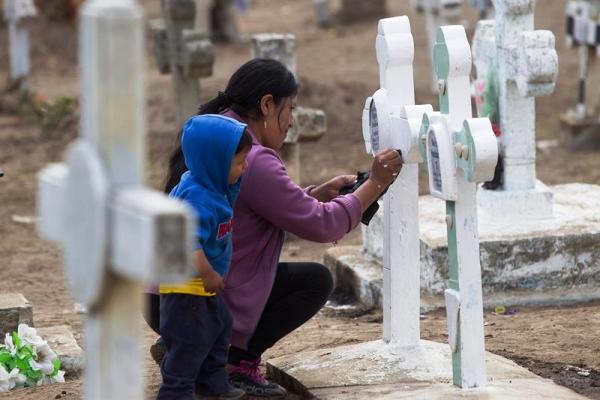 PUNIN (ECUADOR), 02/11/2013.- Una mujer y un niño arreglan una tumba hoy, sábado 2 de noviembre de 2013, en el cementerio de la población de Punin, provincia de Chimborazo (Ecuador), al conmemorarse el Día de los Fieles Difuntos, en el que los ecuatorianos acudieron a los campos santos para visitar a sus muertos y aprovecharon la jornada para limpiar, arreglar las tumbas y orar frente a la última morada de sus seres queridos. EFE/José Jácome