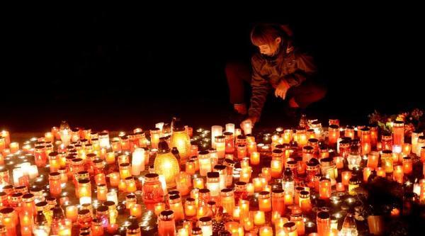 PRAGA (REPÚBLICA CHECA), 01/11/2013.- Una chica enciende velas en una tumba del cementerio Olsany de Praga, República Checa, el 1 de noviembre del 2013, durante la conmemoración de los Fieles Difuntos o festividad de Todos los Santos. EFE/Filip Singer