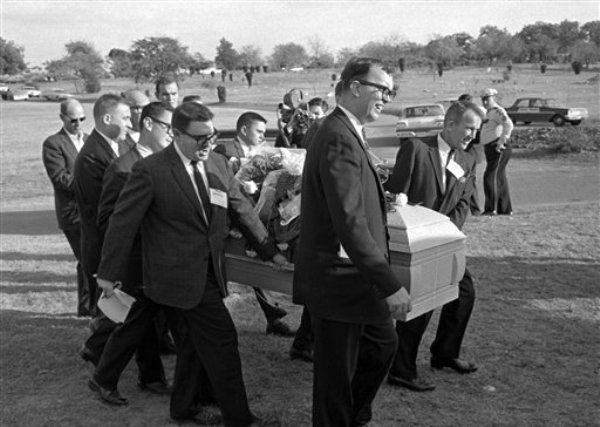 Varios reporteros cargaron el ataúd en el entierro de Lee Harvey Oswald en el Cementerio Shannon Rose Hill. De izquierda a derecha, Jerry Flemmons con cabello cortado a lo militar y sin gafas. Delante de Flemmons van los reporteros Ed Horn y Mike Cochran. El director funerario Paul J. Groody también ayudó a cargar el ataúd. Del otro lado del ataúd están Jon McConal, atrás, y Preston McGraw, al frente. La persona que está detrás de Groody no se pudo identificar. (Foto APo/Gene Gordon)