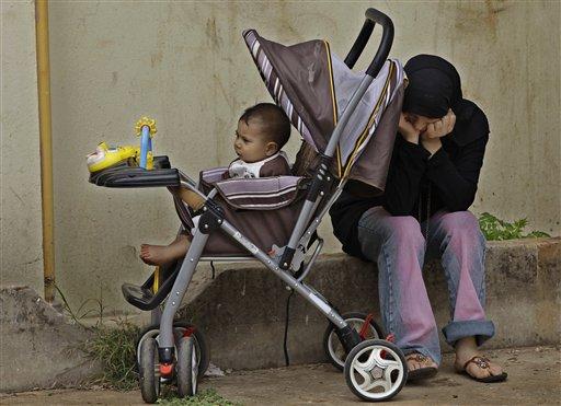 Foto del 30 de mayo de 2012 de una refugiada siria y su hijo que huyeron de su casa en el poblado sirio de Tal-Kalakh. (Foto AP/Hussein Malla, Archivo)