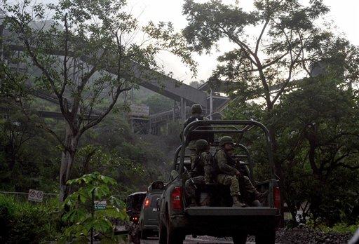Soldados mexicanos entran en la mina de mineral de hierro en Aquila, México, el 14 de agosto del 2013. Una habitante de Aquila dijo que desde el 2012, los Caballeros Templarios han exigido de los habitantes locales parte de las regalías pagadas por una mina de hierro operada por Ternium, un consorcio con sede en Luxemburgo. Los carteles de droga mexicanos, que hace tiempo participan en la piratería, la extorsión y los secuestros, ahora están incursionando en la minería, exportando mineral de hierro a fábricas chinas, dicen autoridades. (Foto AP/Agencia Esquema)