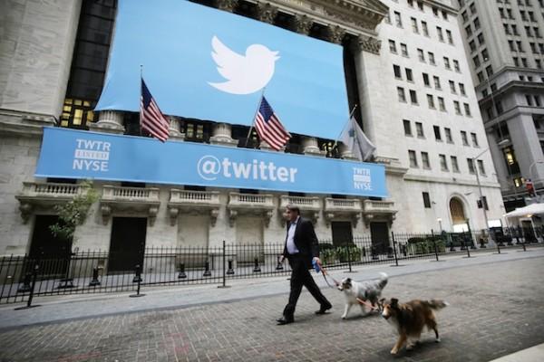 Un hombre camina junto a sus perros frente a la sede de la Bolsa de Valores de Nueva York, que está decorada con el cartel de Twitter, el 7 de noviembre del 2013. Twitter debutó en la bolsa el jueves ante una intensa demanda y un alza en el precio de sus acciones. (Foto AP/Mark Lennihan)
