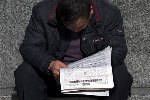 Un chino lee un periódico que reporta que Estados Unidos, Japón t Corea del Sur enviaron vuelos a través de una zona marítima de defensa aérea declarada por Beijing hace una semana en el Mar de China Oriental, el viernes, 29 de noviembre del 2013.  (Foto AP/Andy Wong)