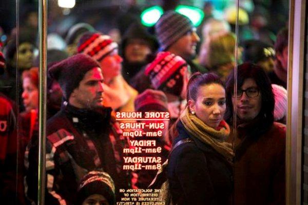 Compradores esperan en línea afuera de las tienda Toys R' Us, en Times Square, Nueva York, el jueves 28 de noviembre de 2013. La temporada de ventas de fin de año en Estados Unidos comenzó aún más temprano el jueves, cuando más de una decena de grandes cadenas minoristas abrieron en el Día de Acción de Gracias a pesar de las protestas de los trabajadores. (AP Foto/John Minchillo)
