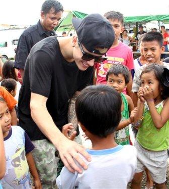 Justin Bieber saluda a niños sobrevivientes del tifón Haiyan durante su visita a la ciudad de Tacloban, en Filipinas, el martes 10 de diciembre del 2013. (AP Foto)