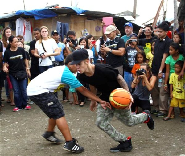 Justin Bieber juega baloncesto con niños sobrevivientes del tifón Haiyan durante su visita a la ciudad de Tacloban, en Filipinas, el martes 10 de diciembre del 2013. (AP Foto)