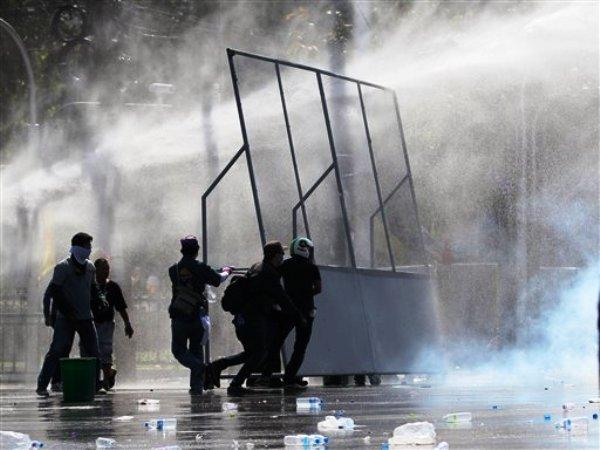 Manifestantes opositores se escudan tras barricadas ante los disparos de cañones de agua y gas lacrimógeno realizados por la policía antimotines en Bangkok, Tailandia, el domingo 1 de diciembre de 2013. (Foto AP/Sakchai Lalit)