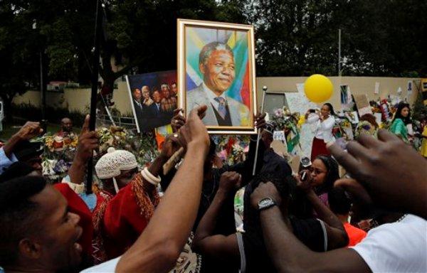 Viajeros de Nigeria cantan frente a la casa del difunto ex presidente Nelson Mandela en Johannesburgo, Sudáfrica, el lunes 9 de diciembre de 2013. En una calle bordeada por mansiones y altas jacarandas, dolientes blancos y negros se congregaron frente a la villa donde murió Mandela, colocaron flores, y notas de condolencia que alcanzaban altura de montículos. Otros bailaban y cantaban alabanzas al líder del movimiento contra el apartheid en una muestra de la unidad multicultural sin distinción de razas que propugnó Mandela para Sudáfrica. (AP Foto/Themba Hadebe)