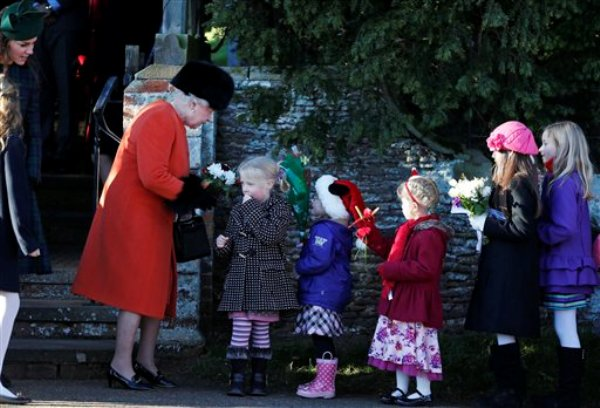 La reina Isabel II de Gran Bretaña recibe flores de parte de niños mientras la Duquesa de Cambridge, a la izquierda, los observa luego de que la familia real británica acudió a la ceremonia de Navidad en la iglesia de St. Mary, en terrenos de la casa de campo de Sandringham, perteneciente a la reina, en Norfolk, Inglaterra, el miércoles 25 de diciembre de 2013. (Foto AP/Lefteris Pitarakis)