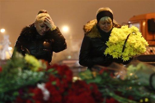 Dos mujeres lloran al colocar flores frente a la principal estación ferroviaria de Volgogrado, Rusia, el 30 de diciembre de 2013.