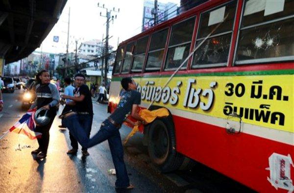 Manifestantes opositores atacan un autobús con personas que sospechan se dirigen a un acto de respaldo al gobierno en Bangkok, la capital de Tailandia, el sábado, 30 de noviembre del 2013. (Foto AP/Wason Wanichakorn)