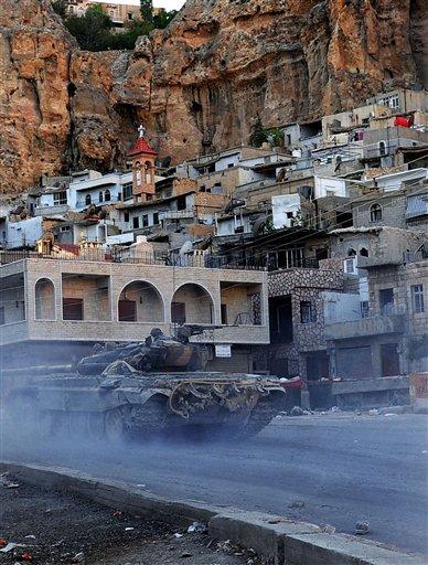 En esta foto de archivo del 11 de septiembre del 2013, dada a conocer por la agencia noticiosa oficial siria SANA, se ve un tanque del ejército sirio durante choques con rebeldes en la aldea cristiana de Maalula, cerca de Damasco. (Foto AP/SANA, Archivo)