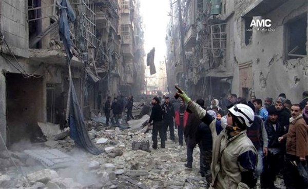 En esta foto del 15 de diciembre del 2015 suministrada por el Aleppo Media Center, cuya autenticidad ha sido verificada en base a su contenido y otras labores noticiosas de la AP, un grupo de sirios inspecciona los daños causados por un ataque aéreo del gobierno en la ciudad de Alepo. Por lo menos 15 personas murieron cuando la aviación siria bombardeó el martes 17 de diciembre por tercer día consecutivo los distritos ocupados por los rebeldes en Alepo, dijeron activistas. (AP Foto/Aleppo Media Center, AMC)