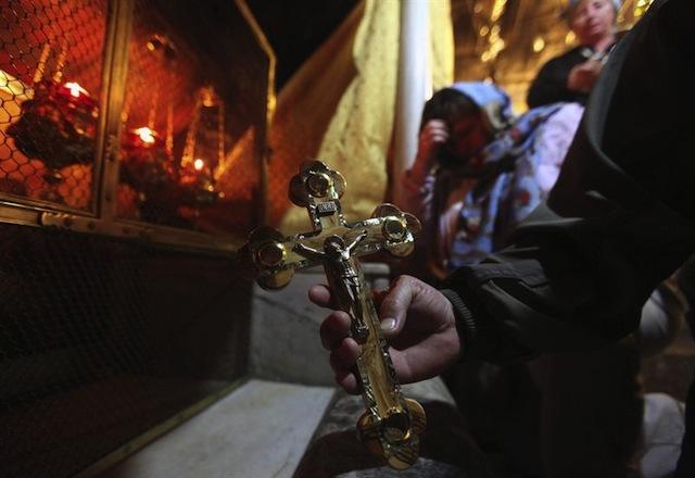 Cristianos rezan en la Gruta de la Natividad, lugar donde tradicionalmente se sitúa el nacimiento de Jesucristo, en la Basílica de la Natividad en Belén (Palestina) hoy, lunes 23 de diciembre de 2013. La nave central está siendo restaurada. EFE/Abed Al Hashlamoun