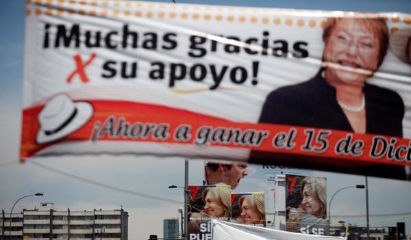 Pancartas de campaña que promueven a las candidatas a la presidencia Michelle Bachelet,y atrás, a Evelyn Matthei cuelgan de los postes de la luz en Santiago, Chile, el jueves 12 de 2013. (AP Photo/Luis Hidalgo)