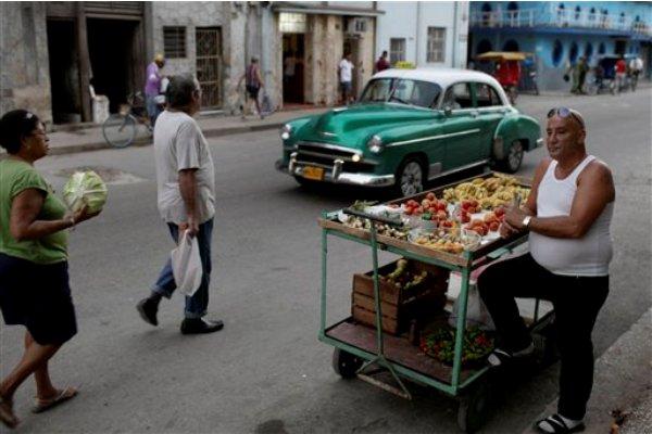 Un vendedor de frutas y vegetales aguarda la llegada de clientes en una calle de La Habana, Cuba, el martes 3 de diciembre de 2013. Algunos cubanos han aprovechado las incipientes facilidades autorizadas por el gobierno para iniciar pequeños negocios. (Foto AP/Franklin Reyes)
