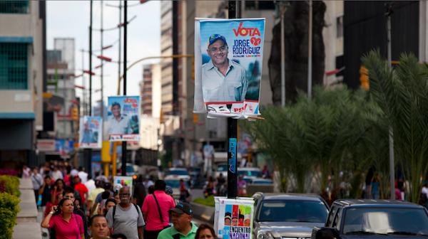 Un grupo de peatones camina por una calle en la que hay anuncios de campaña que promueven al candidato Jorge Rodríguez, en Caracas, Venezuela, el miércoles 4 de diciembre de 2013, unos días antes de las elecciones municipales. (Foto AP/Ariana Cubillos)