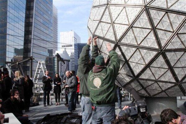 Nick Bonavita (izquierda) y Nick Russomanno (derecha), empleados de Landmark Signs & Electric, instalan un triángulo de cristal Waterford en la esfera de año nuevo durante la presentación a los medios el viernes 27 de diciembre de 2013 en el techo del edificio One Times Square en Nueva York. (Foto AP/Tina Fineberg)