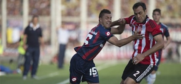 Hector Villalba, left, vies for the ball with Leandro Desabato,