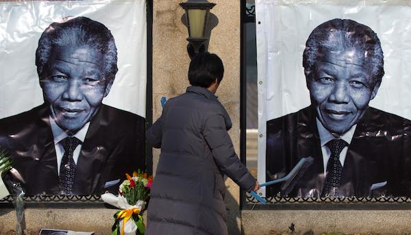 Una mujer limpia un monumento improvisado a Nelson Mandela frente a la embajada sudafricana en Beijing el viernes 6 de diciembre del 2013. (Foto AP/Andy Wong)