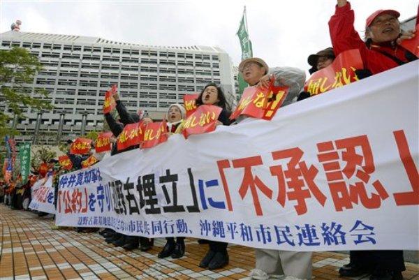 Manifestantes en una protesta contra la reubicación de una base militar estadounidense frente a las oficinas de la prefectura de Okinawa, izquierda al fondo, en Naha, en la prefectura de Okinawa el viernes 27 de diciembre de 2013. El gobernador de Okinawa firmó el viernes 27 de diciembre de 2013 un acuerdo para reubicar la base militar de Estados Unidos en la prefectura. (Foto AP/Kyodo News) JAPAN OUT, CREDIT MANDATORY