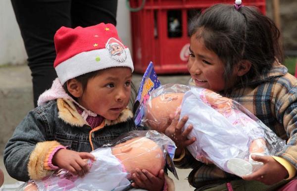 Niñas bolivianas reciben un regalo de Navidad, obsequiado por la campaña decembrina ¿Por la sonrisa de un niñó?, del Grupo de medios Fides y la organizacion juvenil Carros de Fuego, hoy lunes 23 de diciembre de 2013, en La Paz. La campaña entregó este año 35 mil juguetes a niños de escasos recursos. EFE/Martin Alipaz