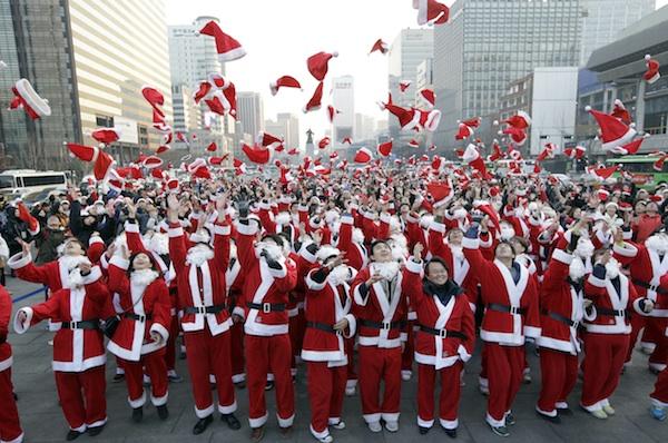 Más de 1.000 voluntarios vestidos como Santa Claus (Papá Noel) lanzan sus gorros al aire al reunirse para entregar regalos a los pobres en el centro de Seúl, Corea de Sur, el martes 24 de diciembre de 2013. (Foto AP/Lee Jin-man)