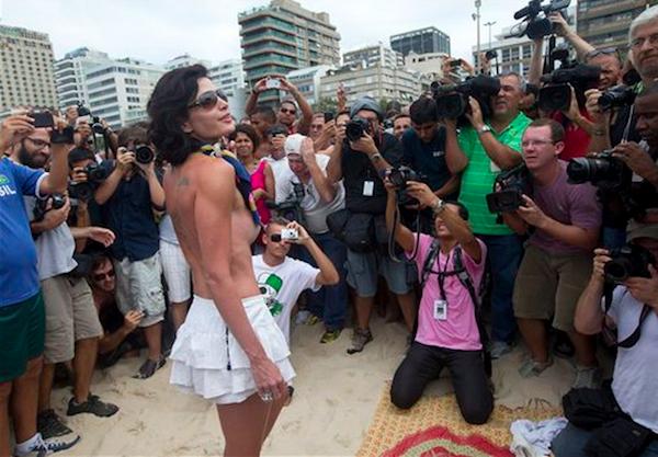 Una mujer posa para los fotógrafos durante una manifestación en la que se pidió el retiro a la prohibición de que las mujeres se asoleen sin la parte superior del traje de baño en la playa de Ipanema beach, en Río de Janeiro, Brasil, el sábado 21 de diciembre de 2013. (Foto de AP/Silvia Izquierdo)