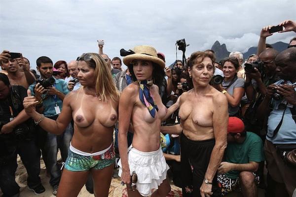"""Tres mujeres con los senos desnudos posan para fotógrafos y camarógrafos durante una protesta hoy, sábado 21 de diciembre de 2013, en la playa de Ipanema, una de las más conocidas de Río de Janeiro, donde decenas de personas se congregaron para exigir la legalización del """"topless"""". EFE/ Marcelo Sayão"""