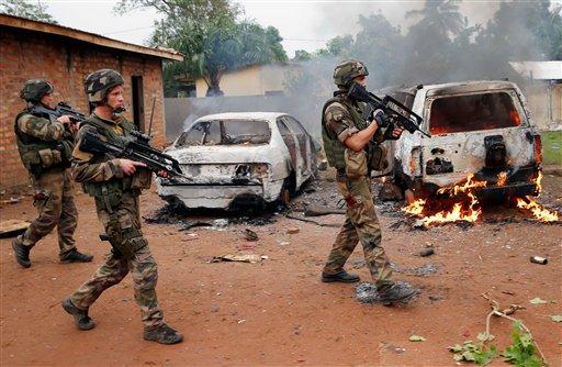 Soldados franceses pasan junto a dos vehículos de la Seleka, una alianza de grupos rebeldes en su mayoría musulmanes, incendiados por turbas cristianas en Bangui, capital de la República Centroafricana, el lunes 9 de diciembre de 2013. (Foto AP/Jerome Delay)