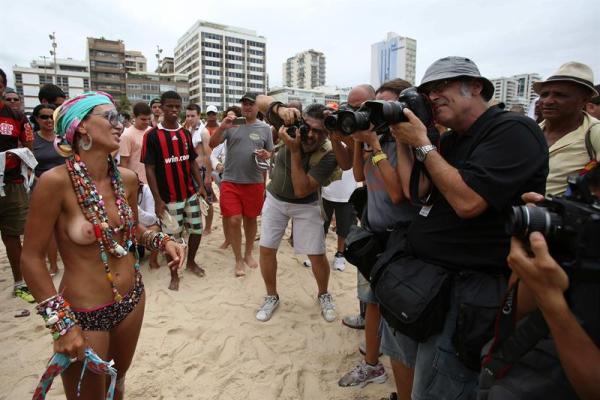 """La argentina Natalia Lorenzo con los senos desnudos posa para fotógrafos y camarógrafos durante una protesta hoy, sábado 21 de diciembre de 2013, en la playa de Ipanema, una de las más conocidas de Río de Janeiro, donde decenas de personas se congregaron para exigir la legalización del """"topless"""", que está prohibido en esa ciudad brasileña por leyes dictadas en """"defensa de la moral"""". La convocatoria para el llamado """"toplessazo"""" se regó por las redes sociales para el primer día del verano carioca para protestar contra la """"arbitrariedad"""" que supone esa prohibición. EFE/ Marcelo Sayão"""
