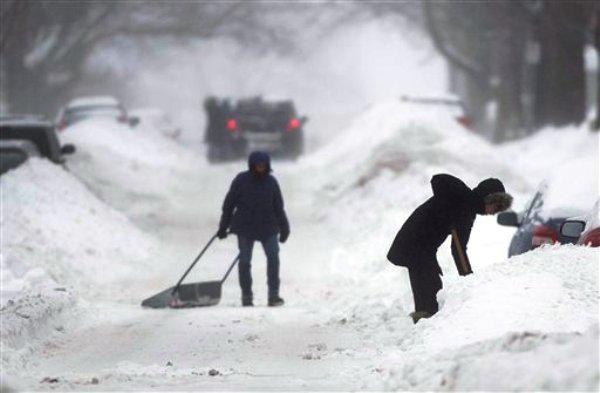 Unas personas palean la nieve en una calle de Montreal, Canadá, el domingo 22 de diciembre de 2013. Más de 500.000 casas y negocios seguían el martes 24 sin electricidad en partes del centro y noreste de EEUU y también en Canadá después de una intensa tormenta invernal en la región que dejó al menos 17 personas muertas. (Foto AP/The Canadian Press, Graham Hughes)